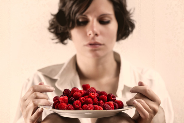 Woman holding a bowl of raspberries
