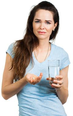kvinde med glas med vand og piller