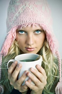 pige med hue som holder en kop grøn te