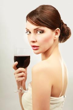 kvinde i hvid kjole med et glas rødvin
