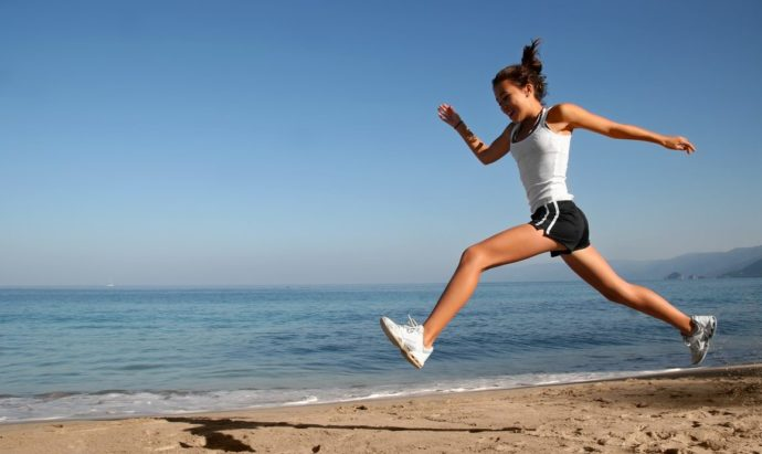 slank kvinde der løber på strand